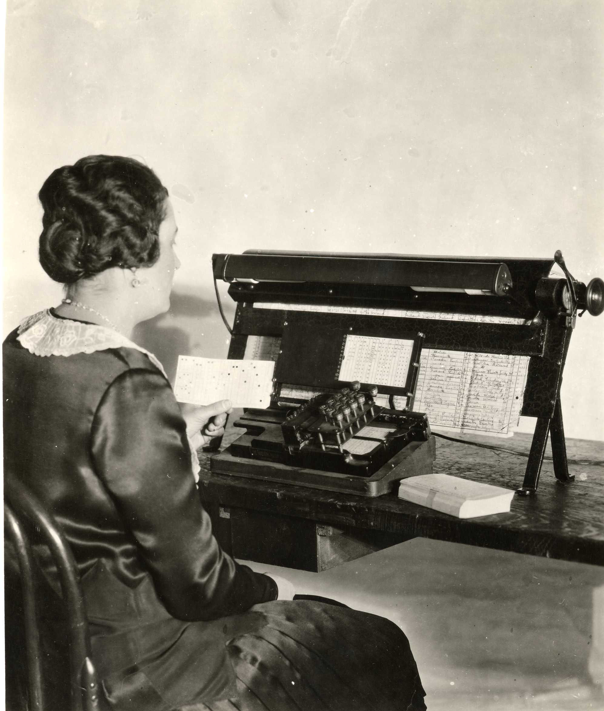Woman working using punch card machine